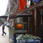 De Javastraat: het economische hart van de buurt. Aan de gevels wapperen Nederlandse, Surinaamse en Marokkaanse en allerlei andere vlaggen naast elkaar.