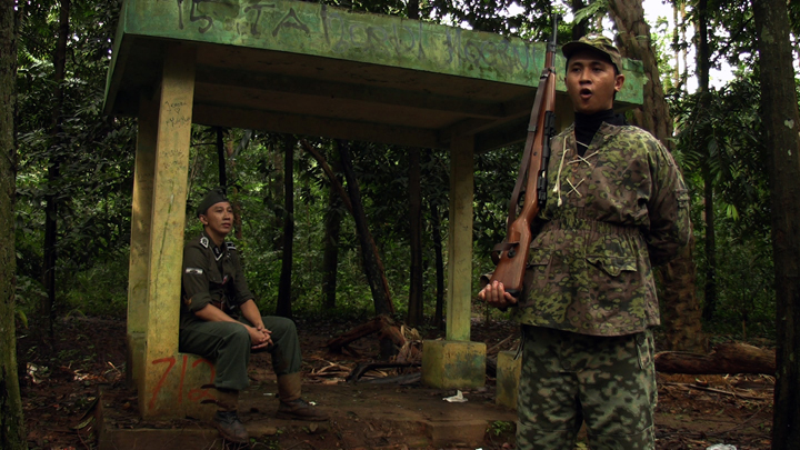 Video still taken from the Empire Indonesia film. Permadi watches one of his soldiers sing a German song. Jakarta, Indonesia. Credit: Eline Jongsma and Kel O'Neill, 2011