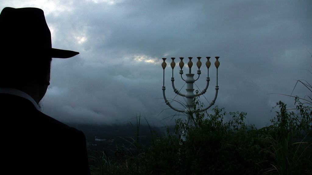 Video still taken from the Empire Indonesia film. Yaakov contemplates life in front of a giant Menorah. North Sulawesi, Indonesia. Credit: Eline Jongsma and Kel O'Neill, 2011