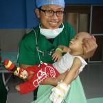 Indonesische chirurg met geopereerd kindje